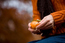 A woman peeling a clementine, close up